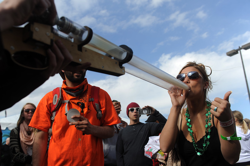 DENVER, CO - APRIL 19: Kimberly Bullard, 23, of Los Angeles, California takes a hit off a I420 Double Barrel Shotgun pipe during the High Times Cannabis Cup at the Denver Mart in Denver, Colorado on April 19, 2015. The High Times Cannabis Cup runs through Monday at the Denver Mart. (Photo by Seth McConnell/The Denver Post)
