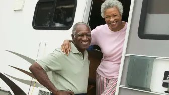 A senior couple in the doorway of their RV, smiling