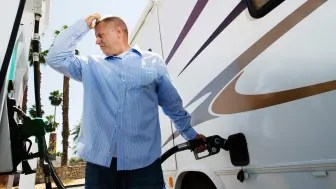 Senior man filling up his RV at a gas pump
