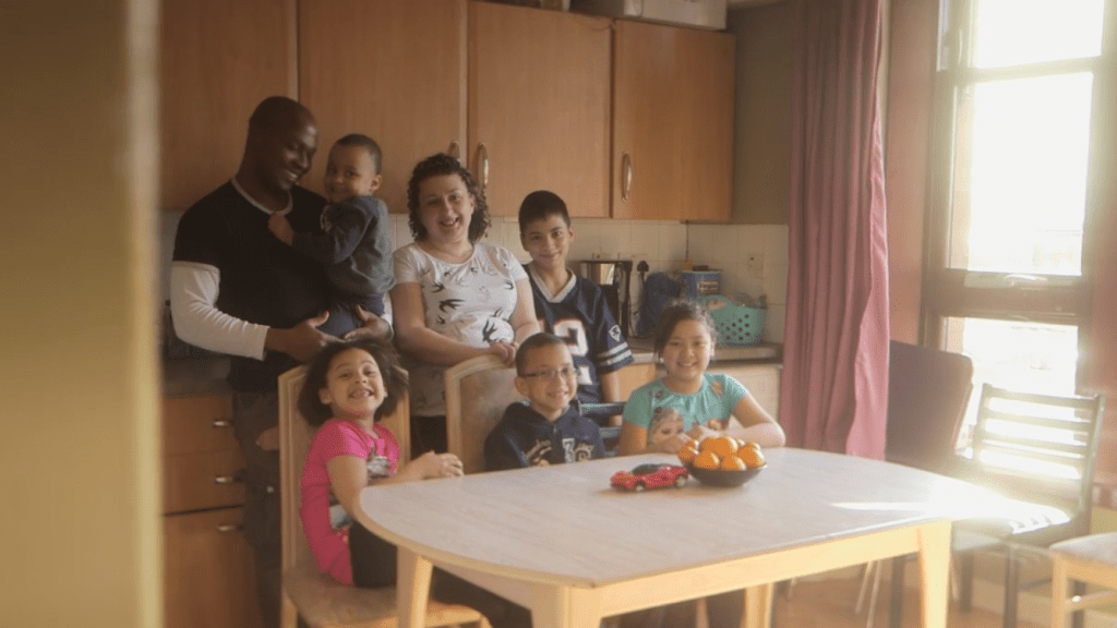 Family together in kitchen of house in Shettleston, looking happy