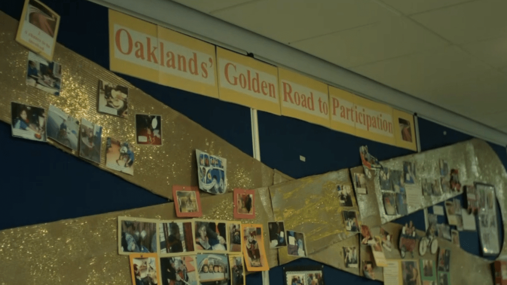 Display wall in school charting Oaklands' Golden Road to Participation with photos