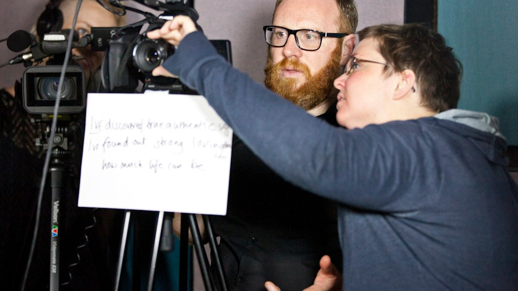 Woman showing man how to operate a camera, both looking at camera