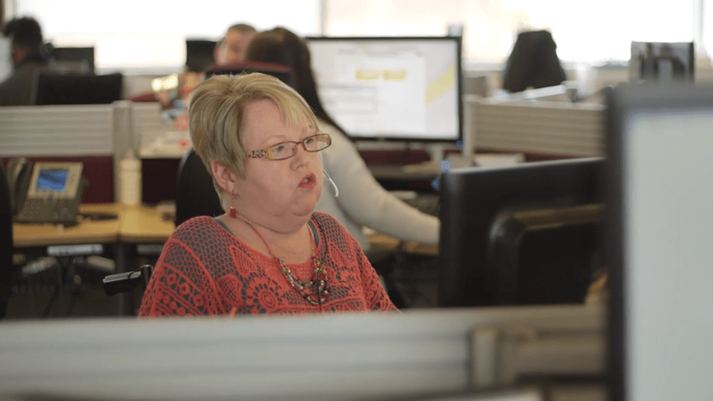 Joan on a call at her computer with colleagues visible in the background