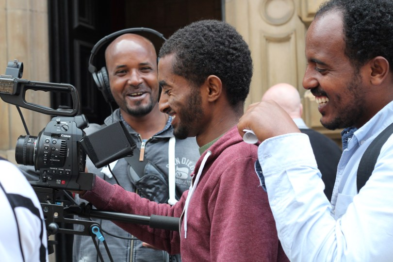 Three male participants filming and enjoying themselves with smiling faces