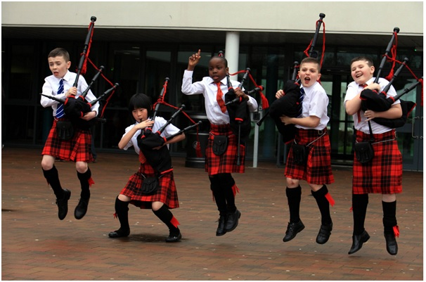 The Wee Govan Pipers with bagpipes and kilts jumping in the air