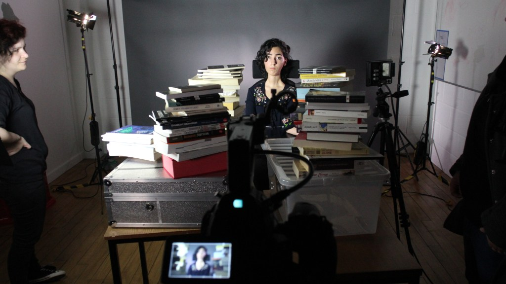 Kiana Kalantar-Hormozi surrounded by piles of books, lights and camera
