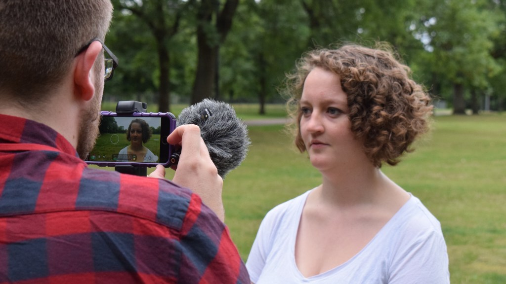 Woman being filmed by a man on a mobile phone in the park