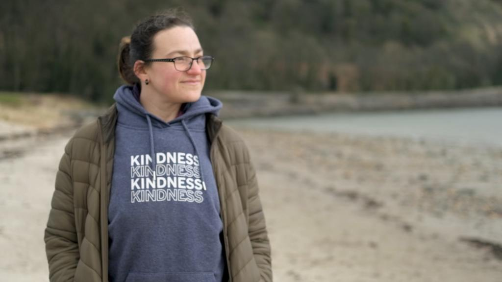 A woman stands on a beach and looks out at the ocean. Her hoodie has the words