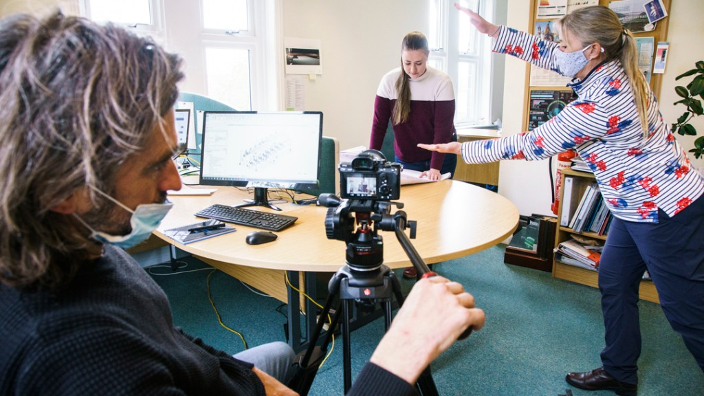 A man with a camera filming a young woman in an office.