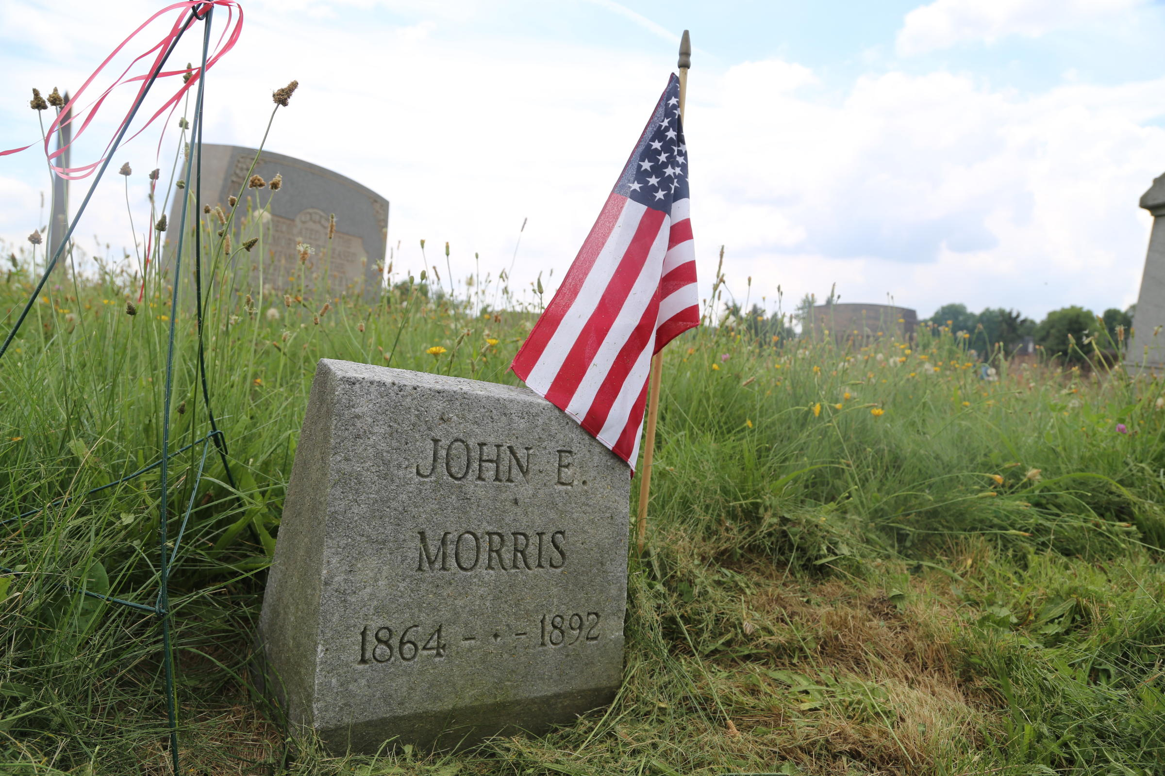 Small U.S. flag flies at the grave of John Morris, the first worker killed in the battle outside of the Homestead Works Steel Mill in 1892. Photo by Alex Popichak / 90.5 WESA