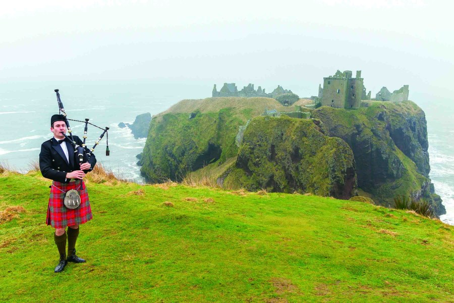 Bagpipe player on top of a hill in Scotland