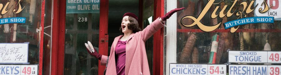 Woman in pink 1950s dress and coat waving her arm at the butcher shop