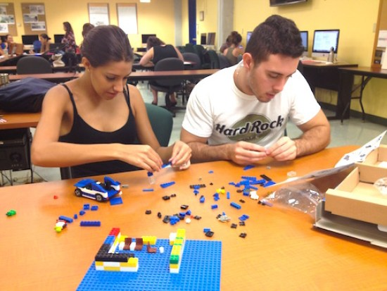 FIU journalism students Melisa Borges and Alex Stella use Legos to promote their journalism research. Photo by Robert Gutsche, Jr.