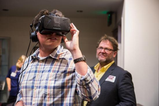 Sports journalism junior Kody Acevedo tries out EcoRift with ASU professor Garth Paine during Innovation Day. EcoRift provides a virtual-reality experience of the desert utilizing 3-D audio and video. Photo by Deanna Dent/ASU Now.