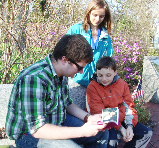 Rutgers student Mike Davis flips through family photos with 9/11 children Dorothea and Rodney Wotton. Photo courtesy of Rutgers University.