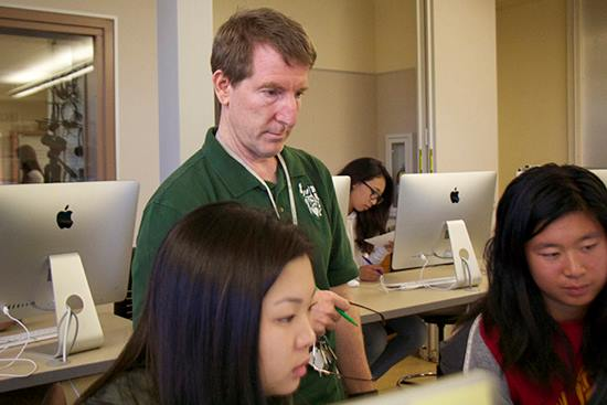 Verde advisor Paul Kandell looks on as students work on their articles in Palo Alto High School's computer lab.