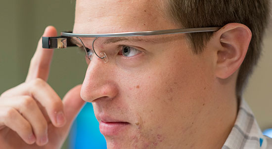 Student journalist Reuben Jones, from New York University, taps Google Glass to record video while experimenting with wearable tech in the ONA14 newsroom.