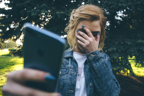 Teen holding her phone in one hand and covering her face with the other hand.