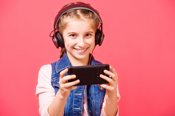 Smiling girl with headphones and mobile phone