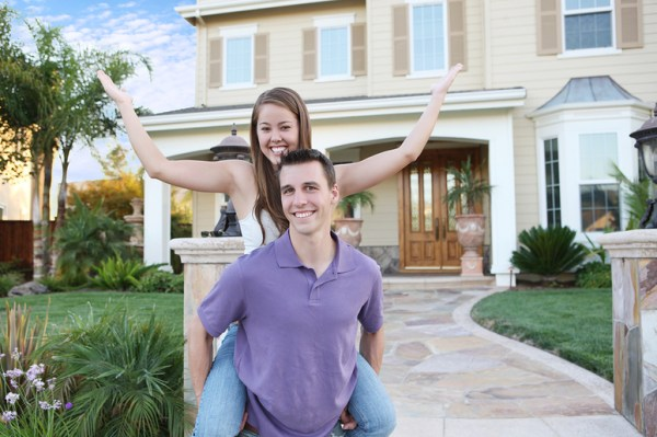 Man and woman in front of a new house celebrating.