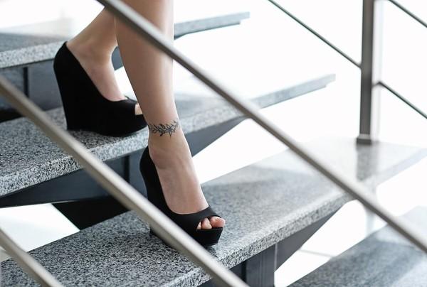 Woman walking down slippery appearing steps.