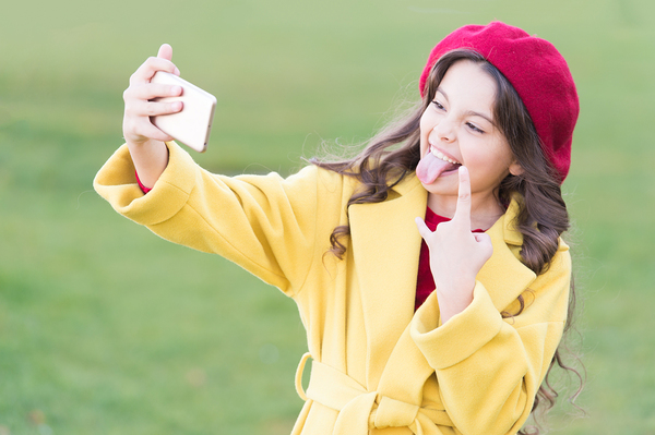 Girl making a funny face while taking a selfie.