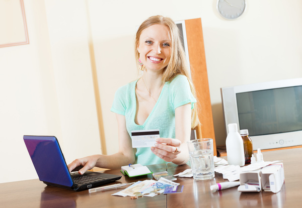 Smiling woman using a credit card to shop online.