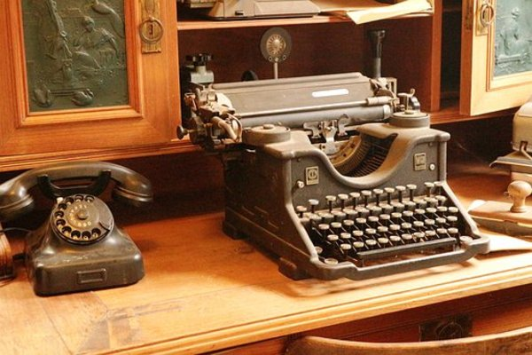 Antique typewriter and telephone on a desk.