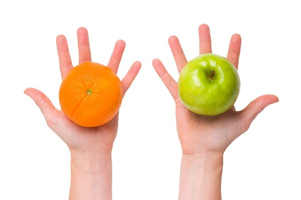 Left hand holding an orange in the palm, and right hand holding a green apple.