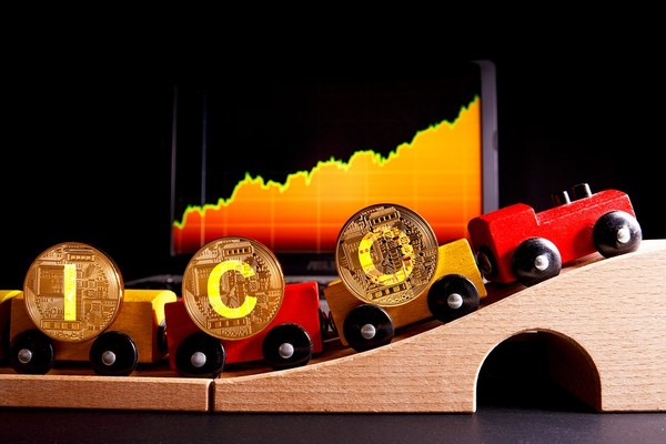 Toy train with gold bitcoins spelling out ICO.