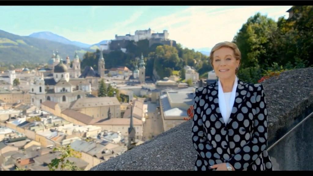 Julie Andrews standing before panarama of Salzburg Austria