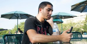 Stony Brook, NY - Fayik Nouri, a freshman biology major at Stony Brook University, focuses on his phone while he sits outside the Student Activities Center at Stony Brook University on Friday, September 5, 2014. If money didn't matter, he said that he would like to work at a record label in New York City.