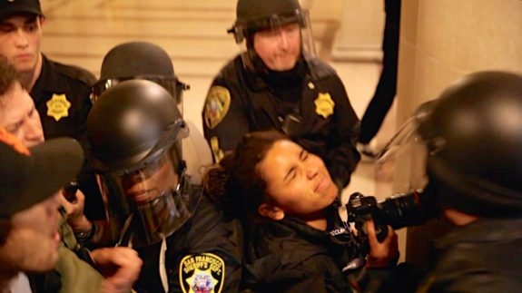 "San Francisco Sheriff Deputies shove photojournalist Gabriella Angotti-Jones who was covering a ""Frisco 5"" protest at City Hall on May 6, 2016. Angotti-Jones, with El Tecolote and CCSF's The Guardsman, was wearing her press credentials. Photo by Noé Serfaty"