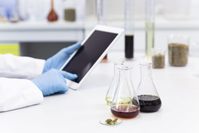 Hands with medical gloves typing on white tablet over laboratory desk. Hemp seeds, marijuana bud, CBD and CBDa oils are on table. Cannabis pharmaceutical healthcare concept.