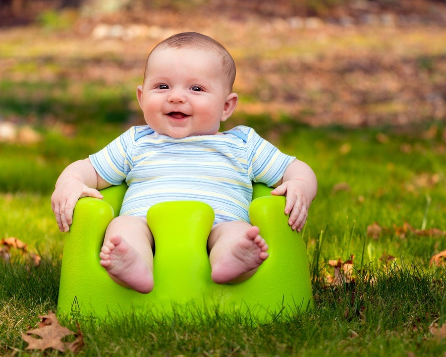 Happy infant baby boy using training Bumbo seat to sit up