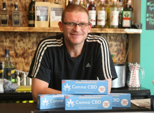 Tim Acton next to CBD products in his hotel Leafy Hotel