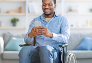 man in a wheel chair with phone