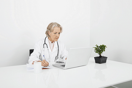 Doctor at computer perhaps working on Electronic Health Records due to Medicare's MACRA