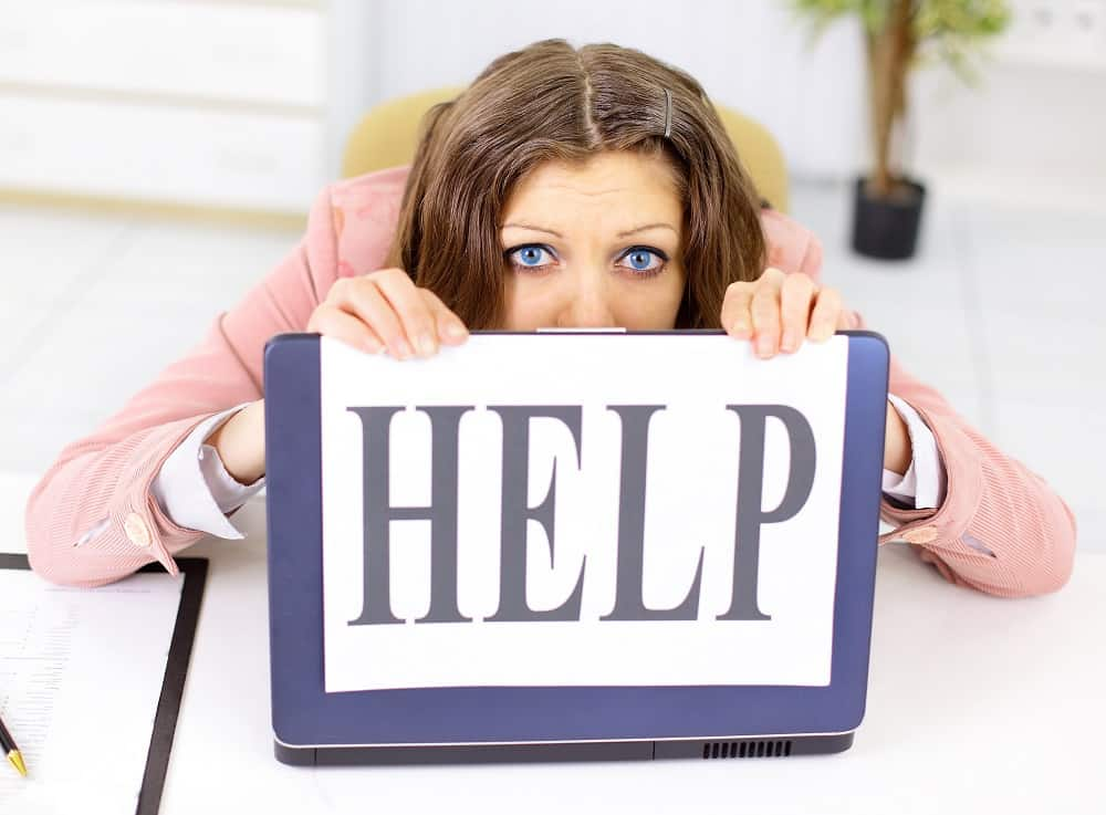 image of woman holding HELP sign at desk which describes how I felt when I found out my dad's Medicare prescription drugs cost $5000 per month