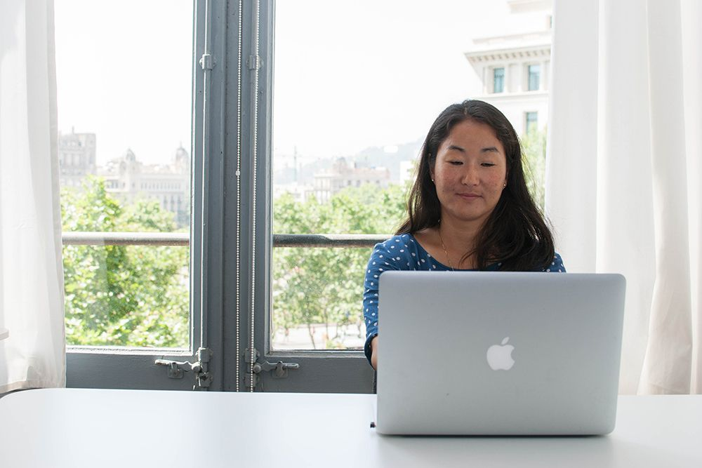 asian woman working on a mac laptop in a bright office