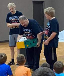 Dan and 2 assistants showing live rabbit to children