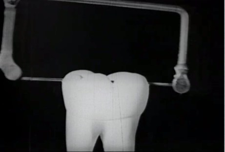 A frame showing a large model tooth being sawn in half from the top down.