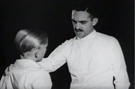 A dentist puts his hand on a boy's shoulder.