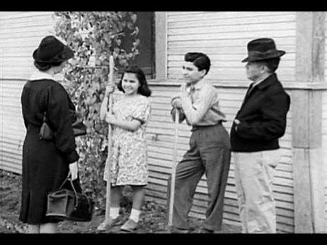 Two children work outside their home in the garden, with their father standing nearby. A visiting nurse speaks to them.