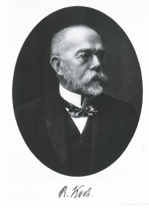 A formal photographic portrait of a man with beard and glasses.