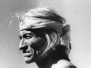 A still frame of a Native American man squinting into the sun.