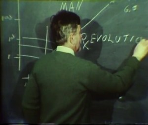 Dr. Calhoun faces a blackboard and writes with chalk: Rx (as in a prescription) followed by Evolution