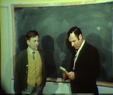 Dr. Calhoun stands next to a dark-haired man with a notebook and pen in his hand, in front of a chalkboard.