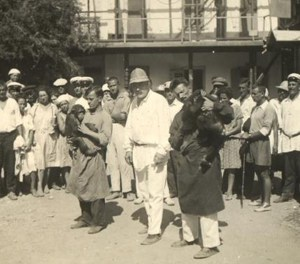 A man in a white suit and pith helmet stands outside in front of a crowd with two men holding apes.