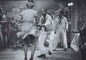 A sailor and a woman jitterbug in a dance hall and bar..